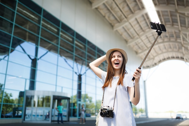 Young ovejoyed traveler tourist woman with retro vintage photo camera doing selfie on mobile phone with monopod selfish stick at airport