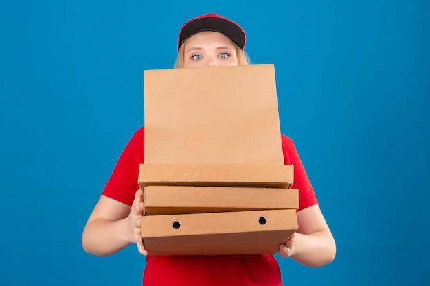 Молодая и напряженная женщина-доставщик в красной рубашке поло и кепке, стоящая со стопкой коробок для пиццы и бумажным пакетом на изолированном синем фоне