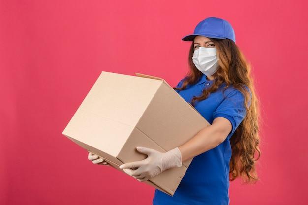 孤立したピンクの背景の上の大きなボックスで立っている医療防護マスクに青いポロシャツとキャップを着た巻き毛の緊張した不機嫌な配達女性以上の若者
