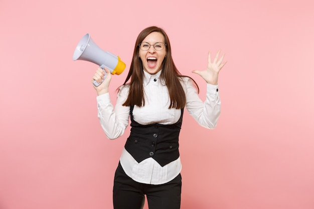 Young overjoyed beautiful business woman in black suit, shirt glasses holding megaphone spreading hands isolated on pink background. lady boss. achievement career wealth. copy space for advertisement.
