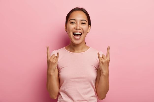Молодая обрадованная брюнетка с азиатской внешностью, позирует с поднятыми рогами и делает рок-жест, оптимистичная и изящная, радостно восклицает, носит повседневную розовую футболку, позирует в