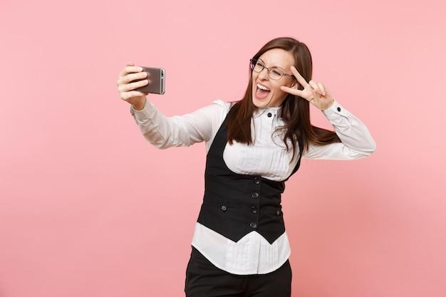 안경을 쓴 젊은 비즈니스 여성은 분홍색 배경에 격리된 승리 표시를 보여주는 휴대폰으로 셀카를 찍고 기뻐했습니다. 여사장님. 성취 경력 부입니다. 광고 공간을 복사합니다.