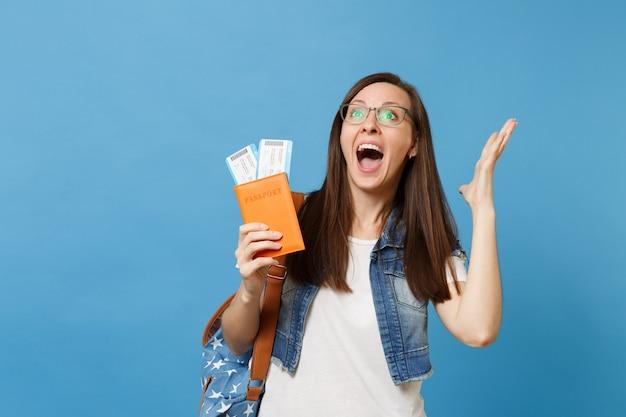 Молодая обрадованная возбужденная женщина с криком студента рюкзака, раздвинув руки, держит паспорт, билеты на посадочный талон, изолированные на синем фоне. обучение в вузе за рубежом. авиаперелет.