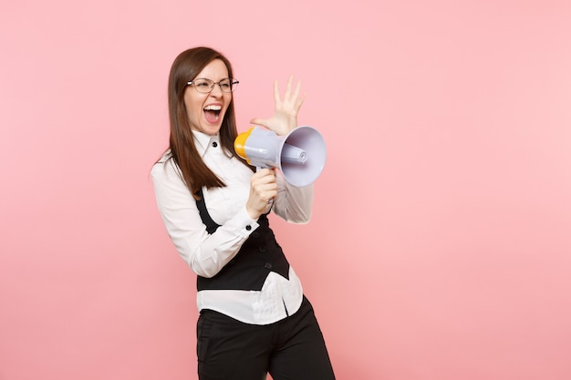 Young overjoyed successful business woman in black suit and glasses holding megaphone spreading hands isolated on pink background. lady boss. achievement career wealth. copy space for advertisement.