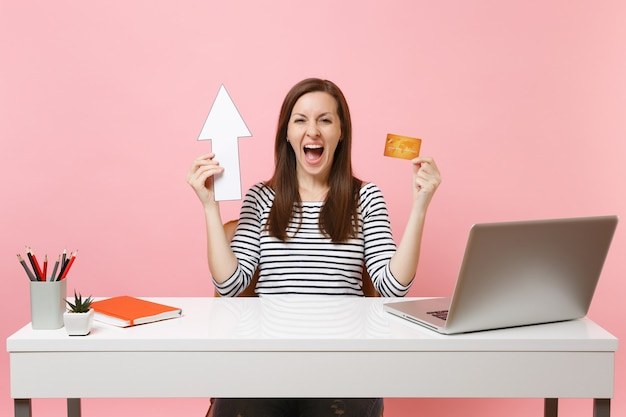 Young overjoyed woman screaming holding up arrow, credit card sit and working at office with contemporary pc laptop