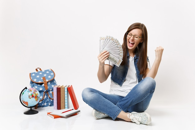 Young overjoyed woman student holding bundle lots of dollars, cash money do winner gesture, say yes near globe backpack books isolated