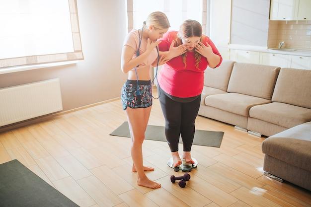 リビングルームで若い太りすぎとスリムな女性