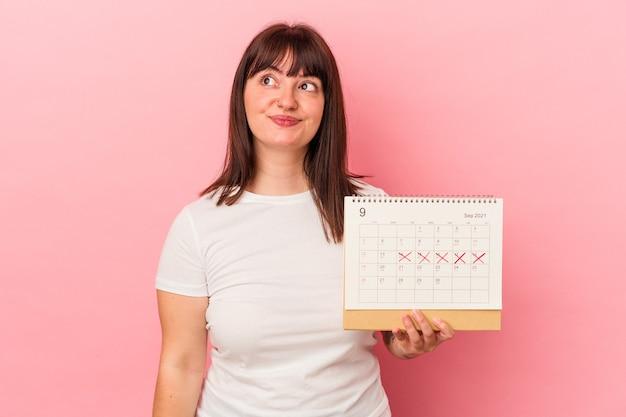 Молодая кавказская женщина, держащая календарь на розовом фоне, мечтает о достижении целей и задач