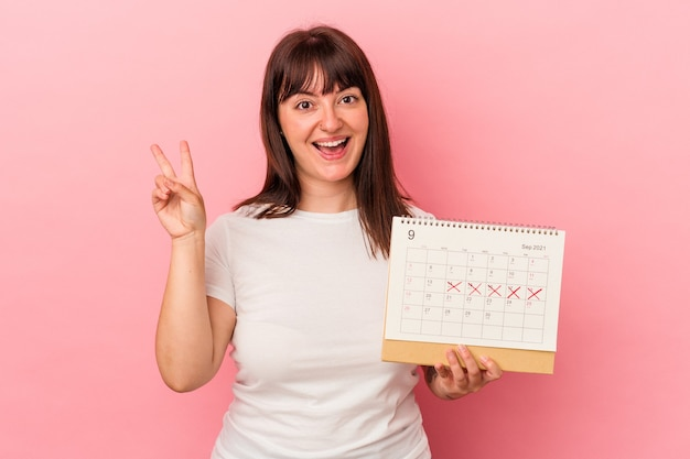 ピンクの背景に分離されたカレンダーを保持している若い太りすぎの白人女性は、指で平和のシンボルを喜んで気楽に示しています。