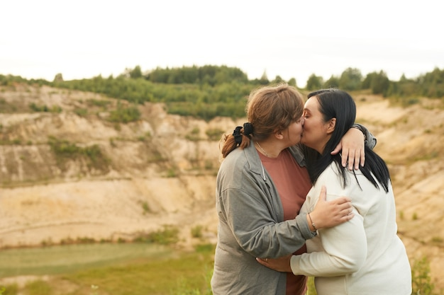 Young overweight lesbian couple embracing and kissing outdoors with beautiful view in the background