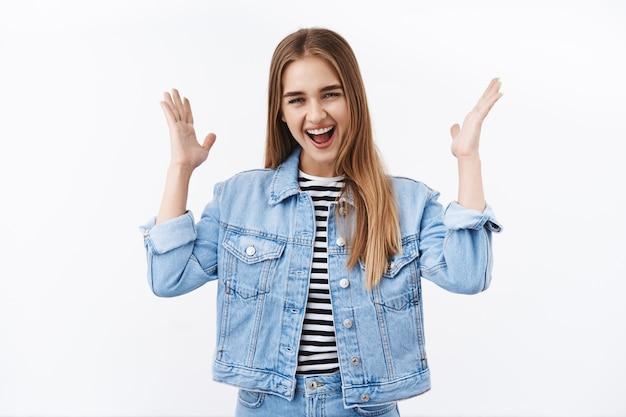 Giovane ragazza bionda felice sopraffatta e sorpresa che celebra grandi notizie, agitando la mano e sorridendo ampiamente, vincendo la competizione, ottenendo un premio, trionfando dalla gioia e dall'allegria