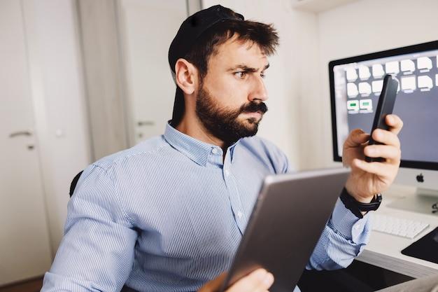 Молодой перегруженный работой бородатый бизнесмен, одетый в деловой повседневный стиль, сидит в своем офисе, используя смартфон и планшет