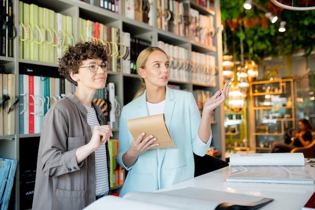 彼女のクライアントに購入するいくつかの項目を示すメモ帳を持つ若い所有者