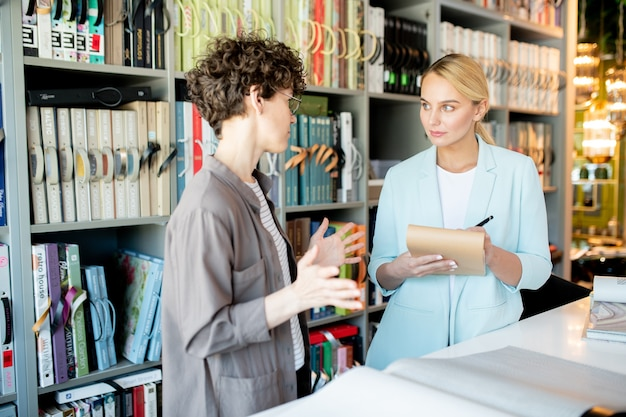 ペンとメモ帳を持つ若い所有者が、女性のクライアントが何を望んでいるかを説明するのを聞く