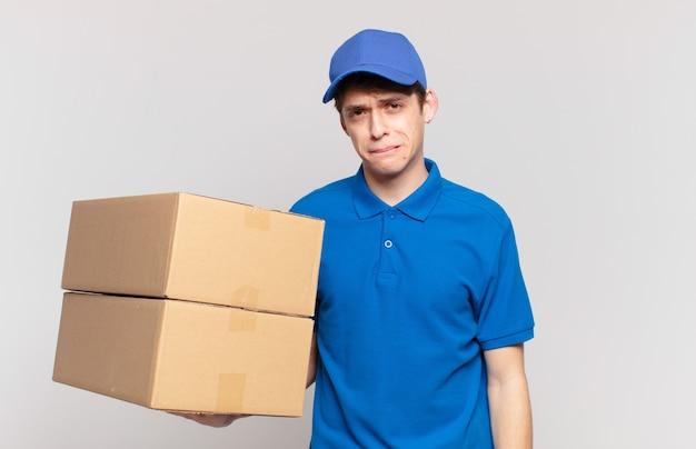 Молодой мальчик-доставщик посылок выглядит озадаченным и сбитым с толку, прикусывает губу нервным жестом, не зная ответа на проблему