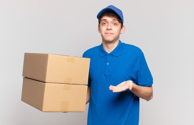 Young package deliver boy shrugging, feeling confused and uncertain, doubting with arms crossed and puzzled look