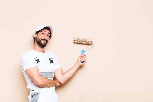 젊은 화가 수염 남자 페인트 롤러로 벽 그림