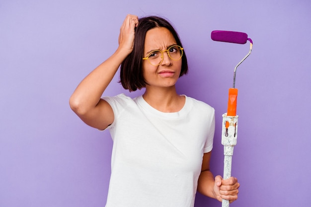 Young painter mixed race woman holding a paint stick isolated on purple background being shocked, she has remembered important meeting.