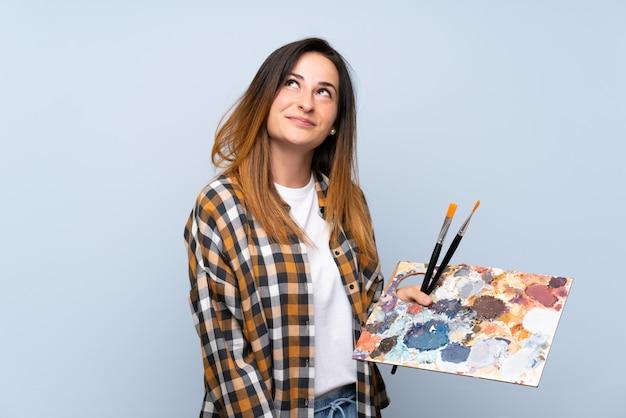 Молодая женщина художника над изолированной голубой стеной смотря вверх пока усмехающся