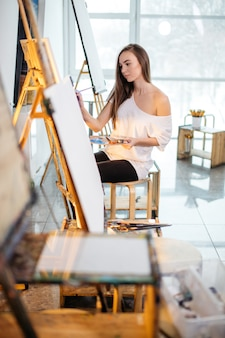 Young painter woman producing picture in art studio