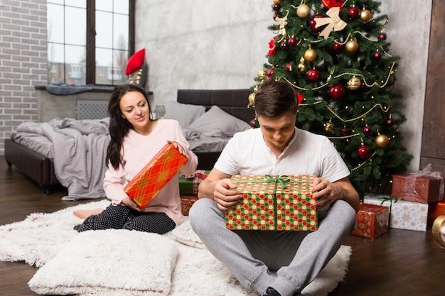 ロフトスタイルの部屋のクリスマスツリーの近くのカーペットに座ってプレゼントを開梱するパジャマの若いペア