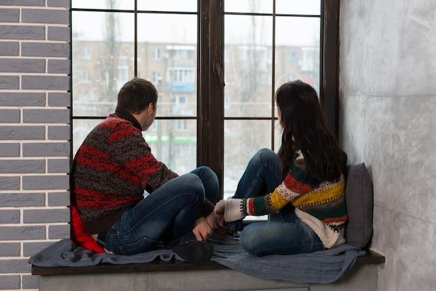 枕と毛布で窓辺に座って窓の外を見ている暖かいニットセーターの若いペア