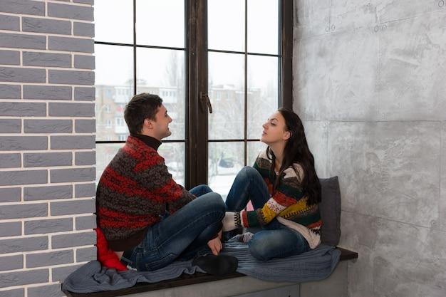 枕と毛布で窓辺に座って話している暖かいニットセーターの若いペア