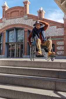 路上で車椅子のラテン系の若者が麻痺し、階段を降りることができない階段の前で欲求不満で憤慨している帽子をかぶっていた