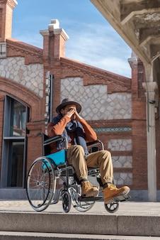 いくつかの階段の前で欲求不満の車椅子の麻痺した若者