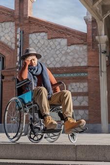 Молодой парализованный человек в инвалидной коляске расстроен перед лестницей