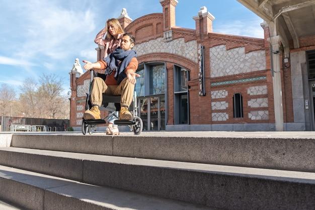Молодой парализованный мужчина с девушкой в инвалидной коляске расстроен перед лестницей