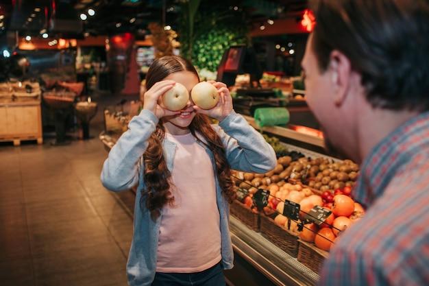 식료품가 게에서 젊은 부모와 딸. 그녀는 사과로 눈을 가리고 미소 짓는다. 아버지는 그녀를 봐. 재미있는 장난 쇼핑.