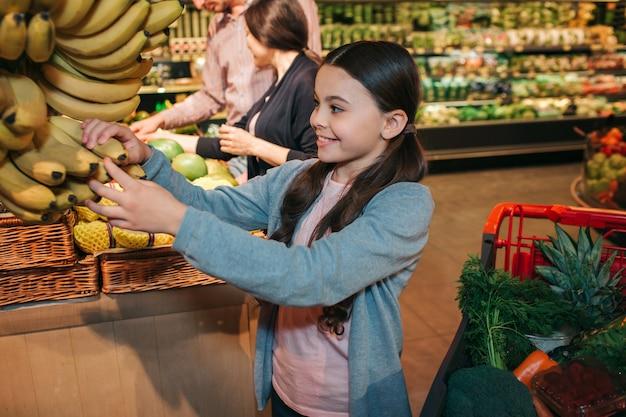 식료품가 게에서 젊은 부모와 딸. 아이는 노란색 바나나를 만지고 미소를 짓습니다. 그녀는 행복하다. 남자와 여자는 뒤에 서서 과일을 선택합니다.