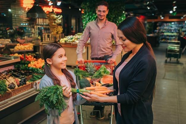 ニンジンを選択する食料品店で若い親と娘