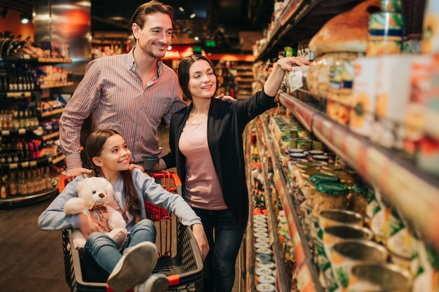 식료품 점에서 젊은 부모와 딸. 그들은 보존을 함께받습니다. 여자는 식료품 트롤리 woth 곰 장난감에 앉아.