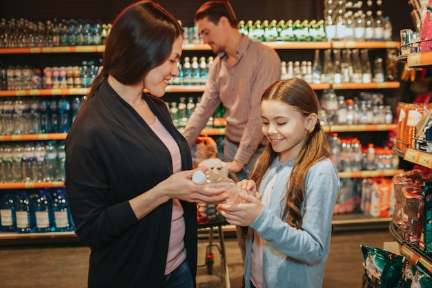 식료품 점에서 젊은 부모와 딸. 여자와 아이 물병을 함께 개최. 아버지는 식료품 트롤리와 함께 뒤에 서 있습니다.