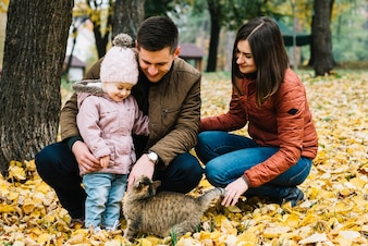 Young parents and little child playing with cat in autumn park