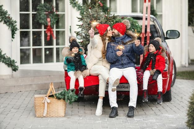 背景に車と家で線香花火を保持している若い親とその子供たちクリスマス休暇のコンセプト