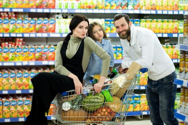 Молодые родители и их милая маленькая дочь улыбаются, выбирая еду в супермаркете