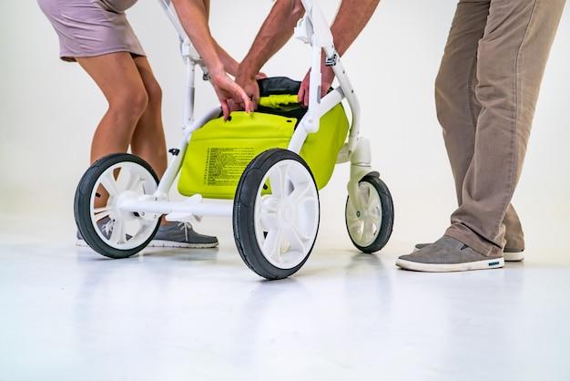 若い親は子供のために緑のベビーカーを準備しています