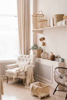 Young parents ' bedroom in beige shades: a feeding chair, a cradle and a scandinavian-style decor