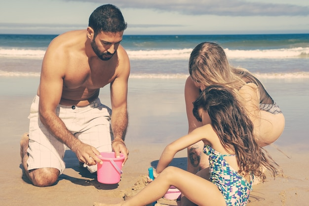 Young parents and cute little girl romping with wet sand on beach, digging with toy shovel, bucket and bowl