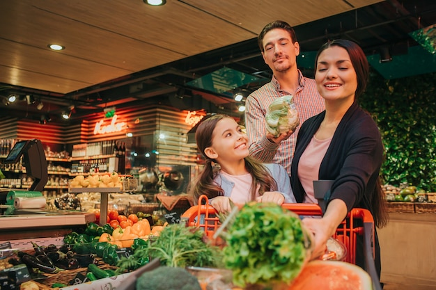 Young parents and daughter in grocery store. father hold cauliflower in hands. mother has lettuce and look at it. daughter smile. she looks at mother.
