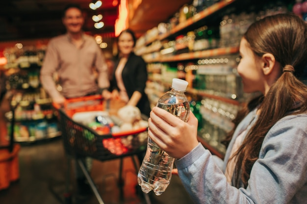 Young parents and daughter in grocery store. little girl hold water bottle in hands and look at parents. they stand behind and carry grocery trolley.