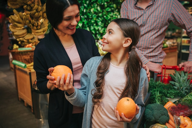 Young parents and daughter in grocery store. little girl look at parents and smile. she hold oranges in hands. father stand behind.