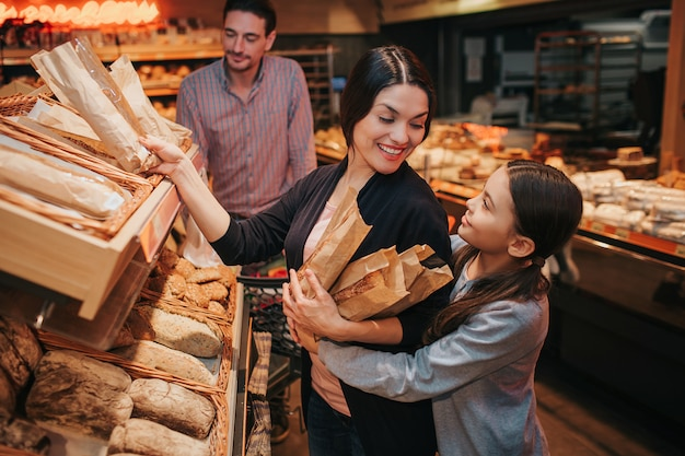 Young parents and daughter in grocery store picking up bread