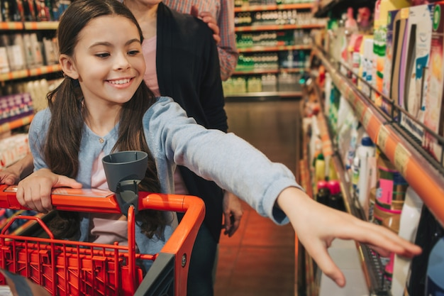 Young parents and daughter in grocery store. small girl reach out to shelf and smile. parents stand behind. girl carry trolley.