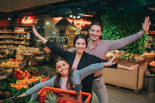 Young parents and daughter in grocery store. they stand behind trolley and pose. people look on camera with smile. cheerful happy family.