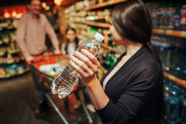Young parents and daughter in grocery store. woman hold water bottle and look at her family. father and daughter stand at grocery trolley.
