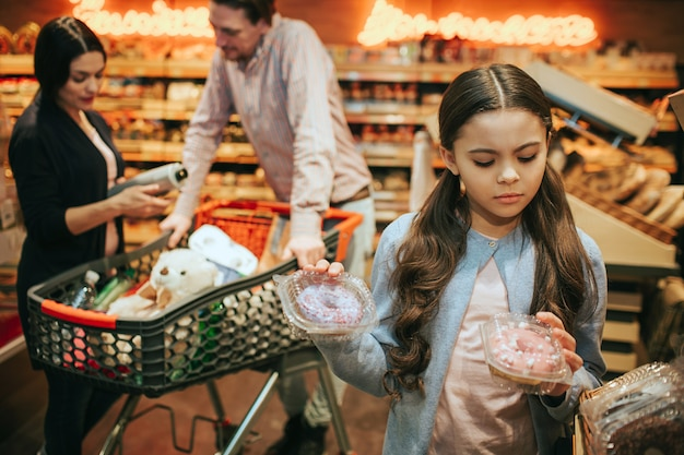 Young parents and daughter in grocery store